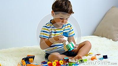 Niño asiático en cámara lenta jugando con coloridos bloques de plástico de construcción en la cama blanca en casa almacen de metraje de vídeo