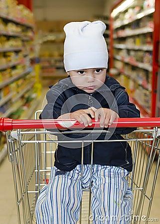 Niño en carretilla de las compras