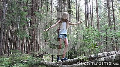 Niño en tronco de árbol de caminata forestal, niño jugando en parque, niña de aventura de camping almacen de metraje de vídeo