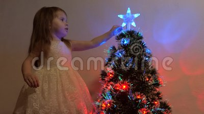 Niño examina una estrella de Navidad en un árbol de vacaciones Niña juega cerca de un árbol de Navidad en una habitación para niñ almacen de metraje de vídeo