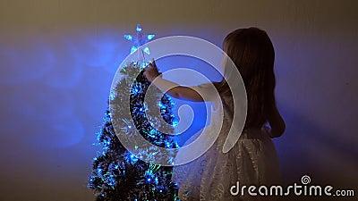 Niño examina una estrella de Navidad en un árbol de vacaciones niñita juega cerca de un árbol de Navidad en un cuarto de niños almacen de metraje de vídeo
