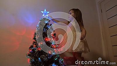 Niño examina una estrella de Navidad en un árbol de vacaciones niñita juega cerca de un árbol de Navidad en un cuarto de niños metrajes