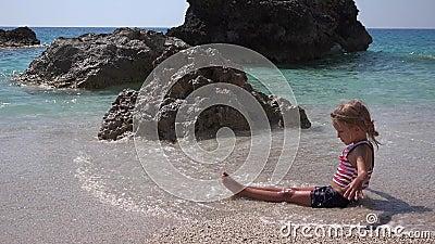 Niño jugando en arena en la playa, niño juega en olas en la orilla del mar, niña construye la bahía del castillo en la costa almacen de video