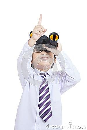 Niño lindo del negocio que sostiene los prismáticos - aislados
