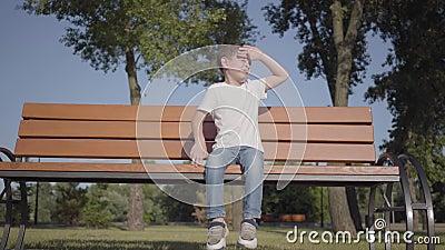 Niño pequeño adorable que se sienta en el banco en el parque Tiempo lindo del gasto del niño solamente al aire libre Ocio del ver almacen de video