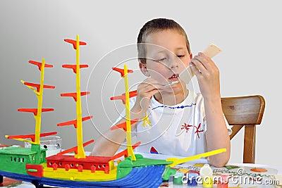 Niño pequeño lindo, nave del sentido de la orientación, pintando