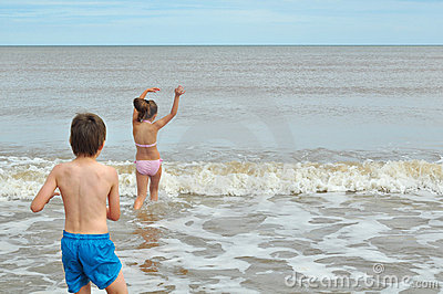 Niño pequeño lindo y muchacha, jugando en onda en la playa
