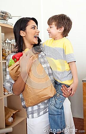 Niño pequeño que desempaqueta el bolso de tienda de comestibles con su madre