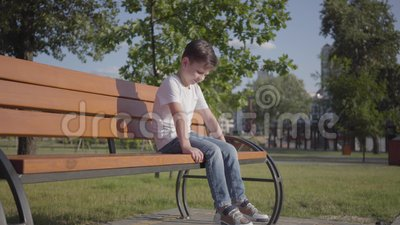Niño pequeño solo triste que se sienta en el banco en el parque Tiempo lindo del gasto del niño solamente al aire libre Ocio del  almacen de video