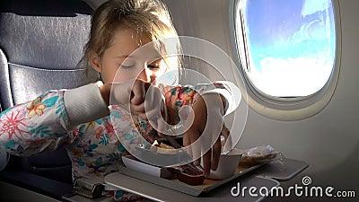 Niño que come el almuerzo sano en aeroplano almacen de video
