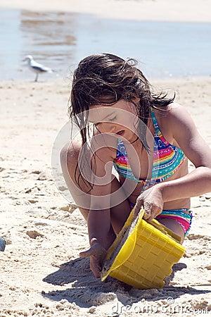 Niño que construye un castillo de la arena