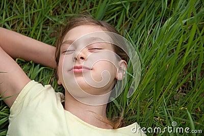 Niño que miente en un prado verde