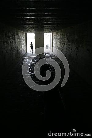 Niño que se ejecuta en sitio oscuro en la fortaleza Desoto, la Florida