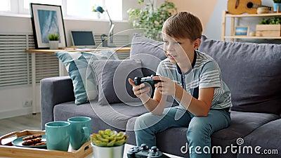 Niño sonriente jugando videojuegos en casa solo divirtiéndose con un dispositivo genial almacen de metraje de vídeo