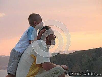 Niño y padre que miran en puesta del sol