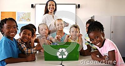 Niños de la escuela que ponen las botellas inútiles en papelera de reciclaje en sala de clase almacen de metraje de vídeo
