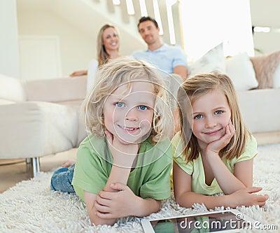 Niños en la alfombra con la tablilla y los padres