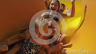 Niños felices yendo con un tobogán a un parque acuático metrajes
