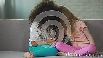 niños Multi-étnicos que se sientan en el sofá y que juegan en el smartphone, tecnología moderna almacen de video