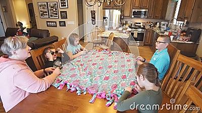 Niños que ayudan a la abuela a atar un edredón en la mesa de comedor almacen de metraje de vídeo