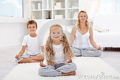 Niños que hacen ejercicio de relajación de la yoga