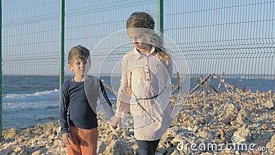 Niños refugiados tristes en la playa cerca de la frontera Región protegida de la valla neta de área restringida Muchacho y niña a almacen de metraje de vídeo