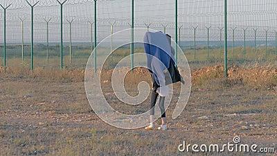 Niños sin hogar caminan cerca de área protegida El tendón cubierto de cabeza de una refugiada florida se extiende a lo largo de l almacen de video