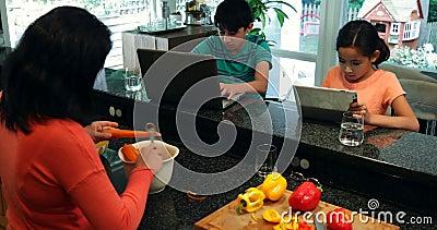 Niños usando el ordenador portátil y la tableta digital mientras que verduras 4k del corte de la madre almacen de video