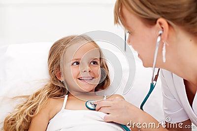 Niña en la cama que tiene una verificación de salud