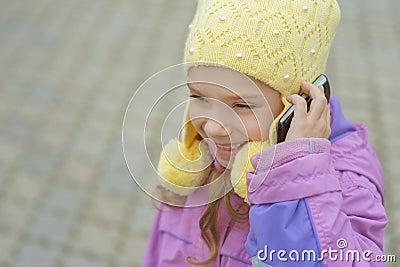Niña sonriente que habla en el teléfono