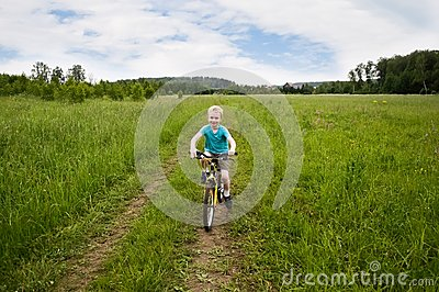 Nice boy cycling in the field