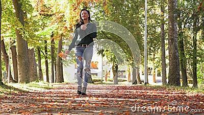 nice brunette girl walking autumn alley holding yellow leaves her hands like fan nice brunette girl walking autumn 161988495