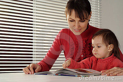 A nice Caucasian mom and daughter holding book