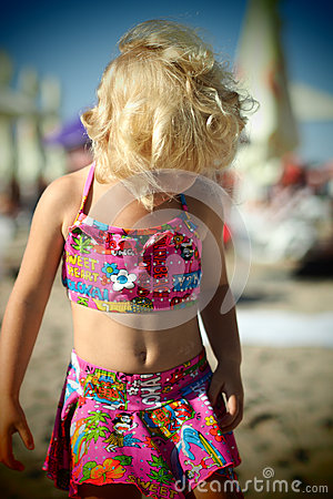 Free Nice Dressed Blond Little Girl On The Beach In The Summertime Looking Down Stock Images - 58131454