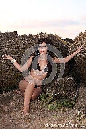 Nice girl in bikini at front of seaside rocks