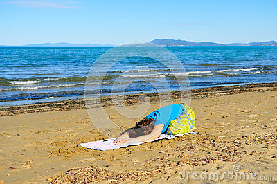 Nice girl doing yoga excercise on the beach