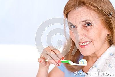 Nice old woman brushing her teeth
