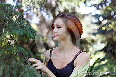 Nice redhead girl near a tree