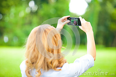 Nice woman taking pictures with smartphone
