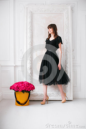 Free Nice Young Blonde Girl. In A Black Dress And Shoes On High Heels. Smelling Flowers Holding Purple Roses Bouquet In Hat Royalty Free Stock Image - 75823846