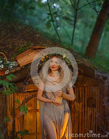 Free Nice Young Girl With Blond Hair With An Amazing Lush Wreath On Her Head In The Forest Is Shaking Herbs. Atmospheric Royalty Free Stock Photo - 132666765
