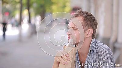 Niechlujny mężczyzna pije alkohol w ulicie piwo w papierowej torbie zdjęcie wideo