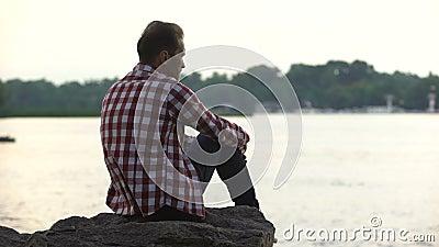 Niedergedrückter erwachsener Mann, der auf Flussufer sitzt und an Scheidung, Einsamkeit denkt stock video footage