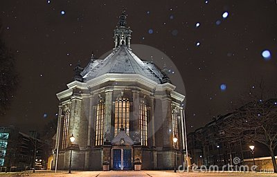 Nieuwe Kerk Den Haag covered in snow at night, while snowing