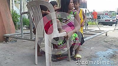 Niezamożny macierzysty być włosy przygotowywającym jej dziećmi, błaga przy kościelnym wrotnym drzwi zbiory