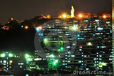 Night cityscape with statue at hilltop