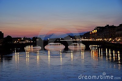 Night lights on the river in Florence city , Italy