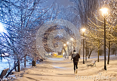 Night running in the snowy park