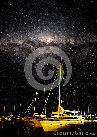 Night sky showing stars and milky way with boats in the foreground