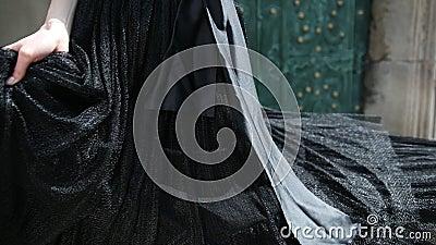 Nikła dziewczyna w czarnej sukni pozuje i wiruje przed kamerą, zdjęcie wideo